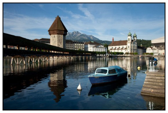 The Chapel Bridge, Jesuit Church and a moored boat, Lucerne, Switzerland.