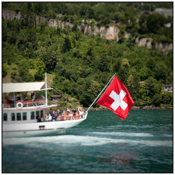 Swiss flag flying off the back of a steam ship on Lake Lucerne