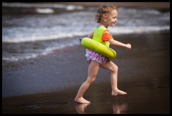 Girl playing on black sand beach, Hana Maui